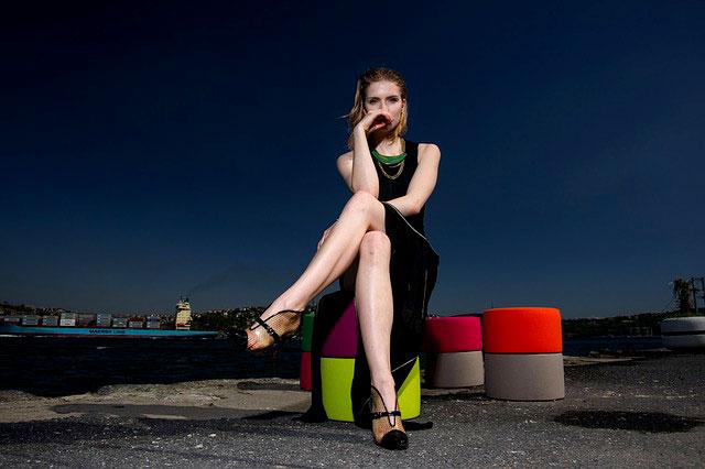 足を組んで座る黒いドレスの女性