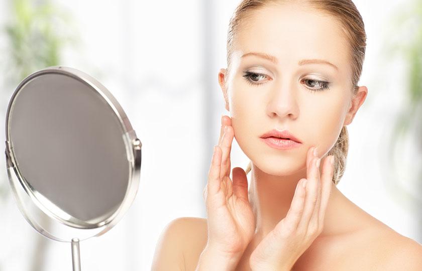 お肌の状態を鏡でチェックする女性