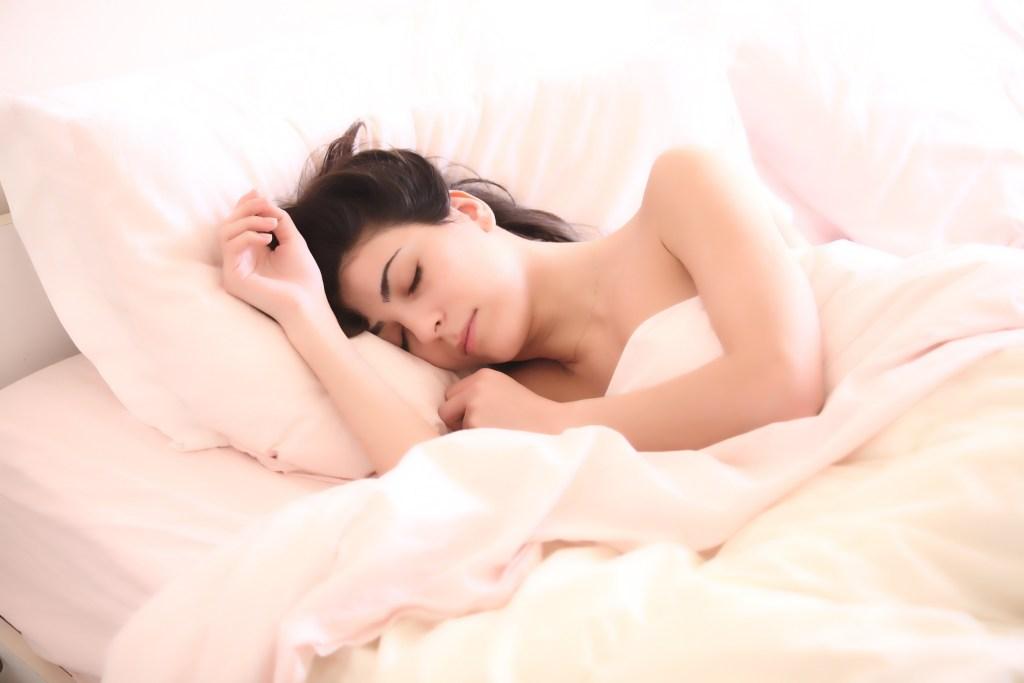 シーツにくるまって眠る裸の女性