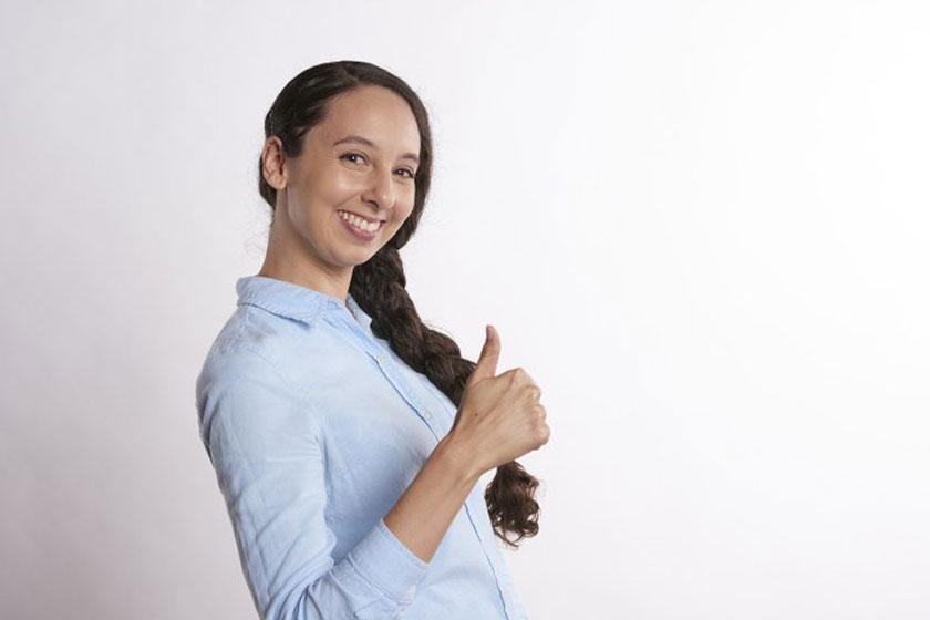 笑顔でサムズアップする女性