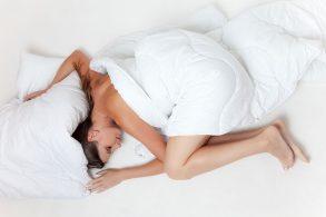 シーツに包まって眠る女性