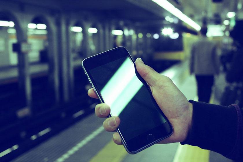 駅でiPhone6sPlusを見る男性