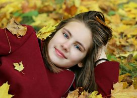 落ち葉の上に寝転がる女性