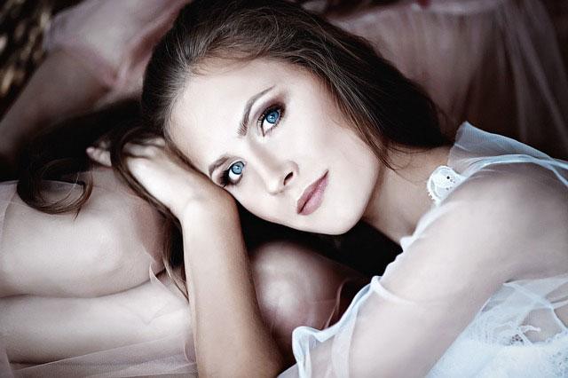 ベッドに横たわってこちらを見つめている若い女性