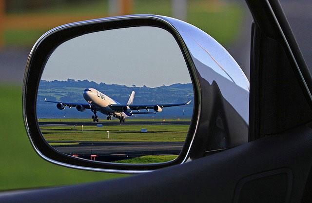 自動車のドアミラーにうつる離陸直前の飛行機