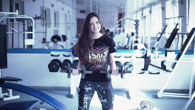 ジムのダンベルで身体を鍛える若い女性