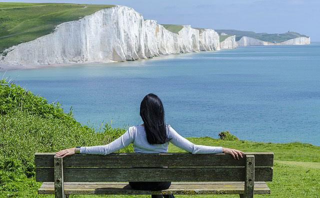 ベンチに腰かけて雄大な自然を眺めている女性