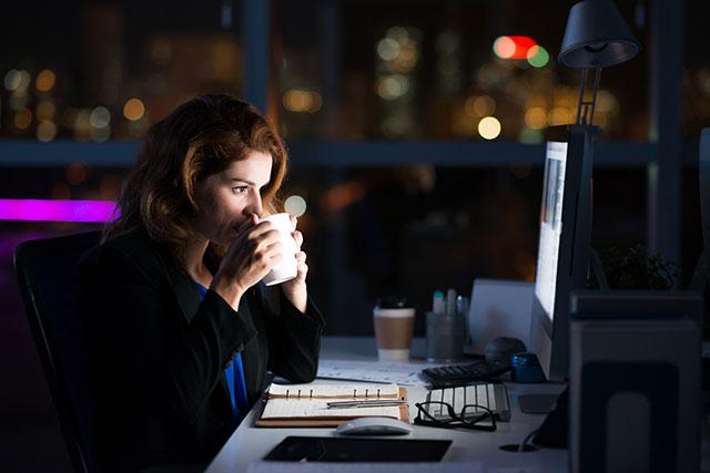 暗いオフィスで深夜残業をする女性