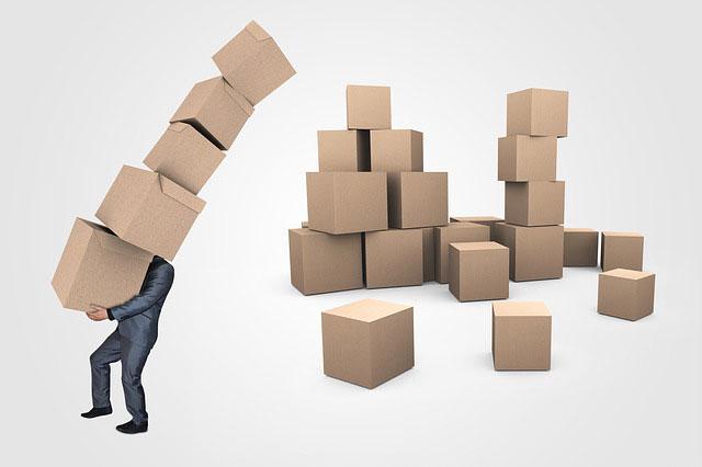 大量の段ボール箱を運ぶビジネスマン