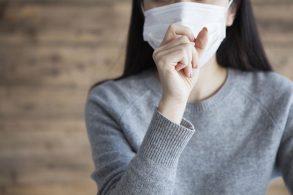 咳をするマスク姿の女性