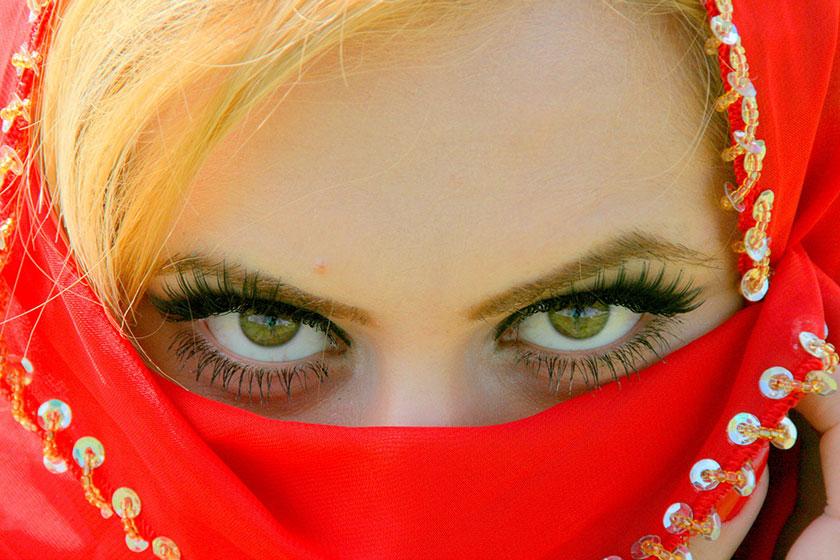 赤い布をかぶった目力の強い女性