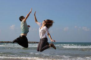 海辺でジャンプハイタッチする男女