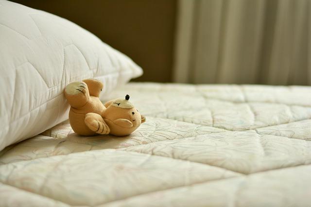 ベッドの上で転がるテディベア