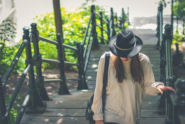 帽子をかぶった女性が階段を上ってくる
